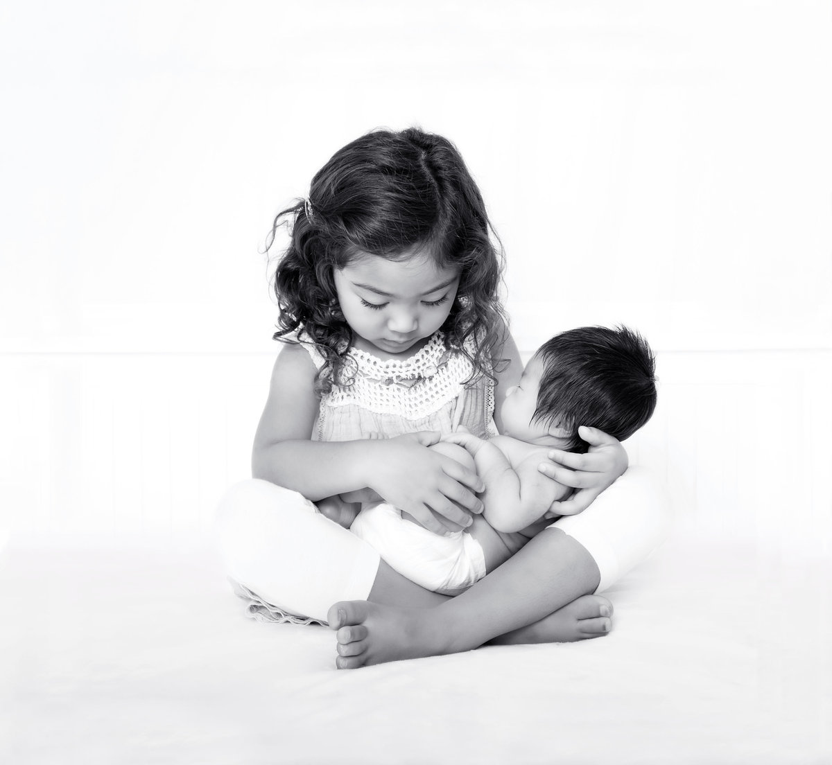 Black and white photo of big sister sitting on the floor cradling his baby sister in her arms as she gently smiles down at her
