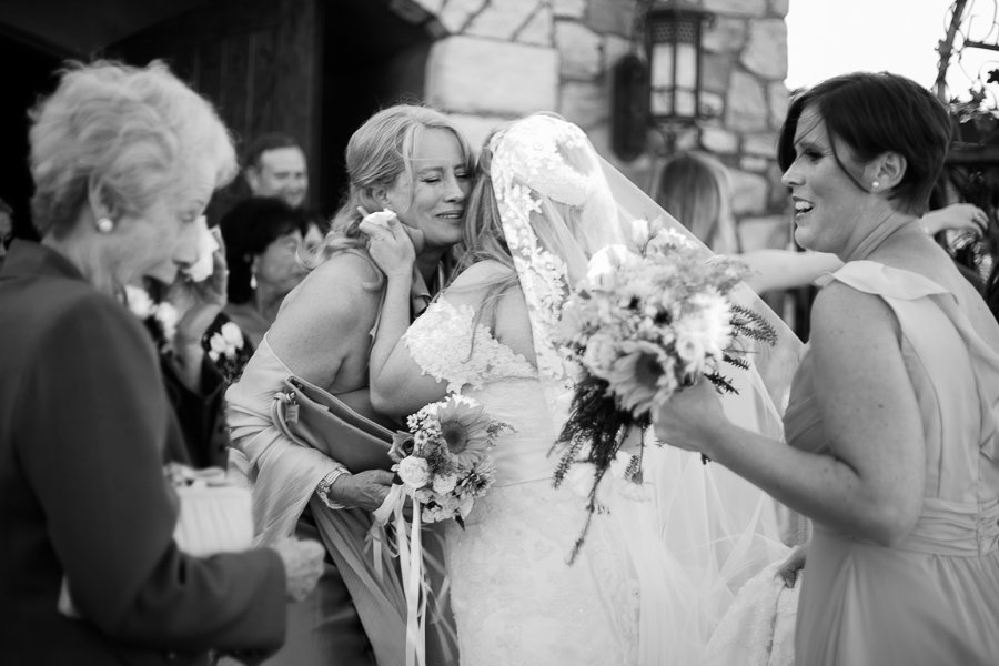Emotional mother hugs daughter after wedding ceremony and grandma wipes tears