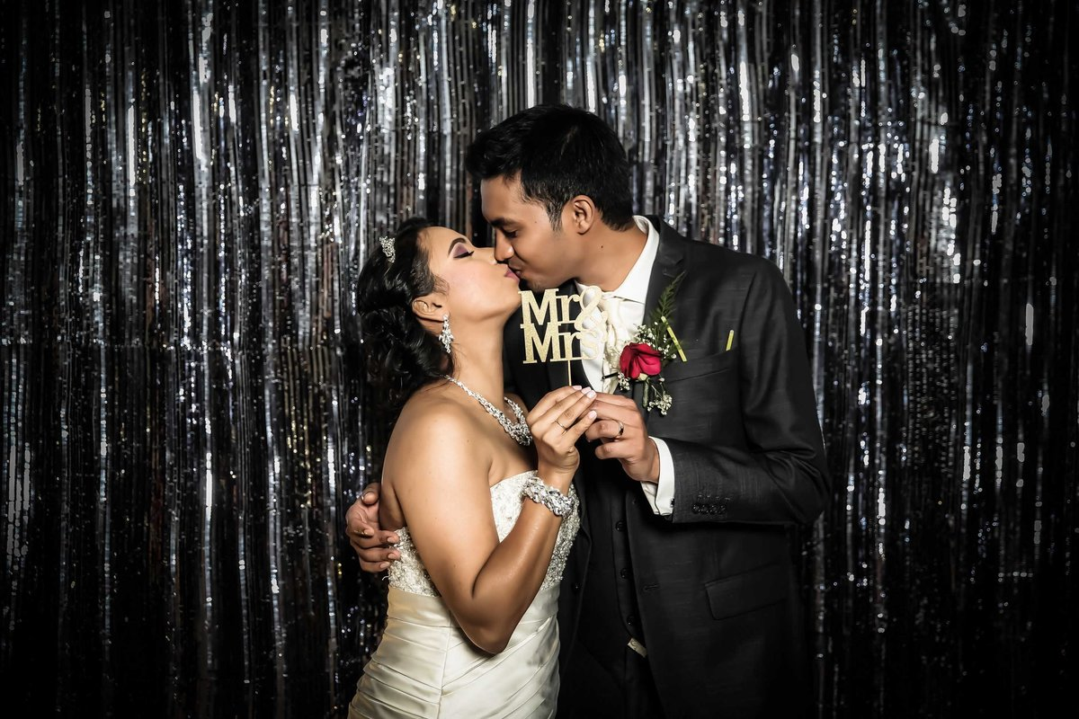 "Bride and groom kiss in front of silver backdrop holding a ""Mr & Mrs"" sign. Photobooth by Ross Photography, Trinidad, W.I.."