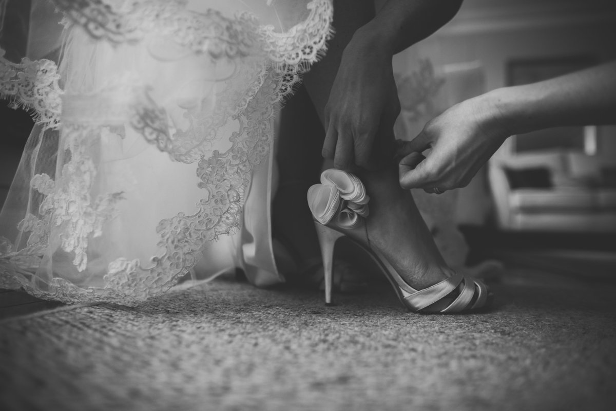 bridesmaid putting shoes on bride