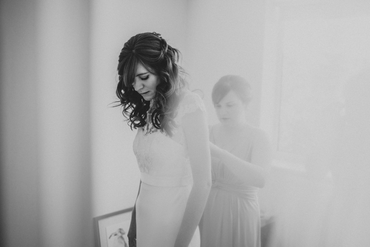 Bridesmaid helping bride into dress - Yorkshire Wedding Photographer Jono Symonds