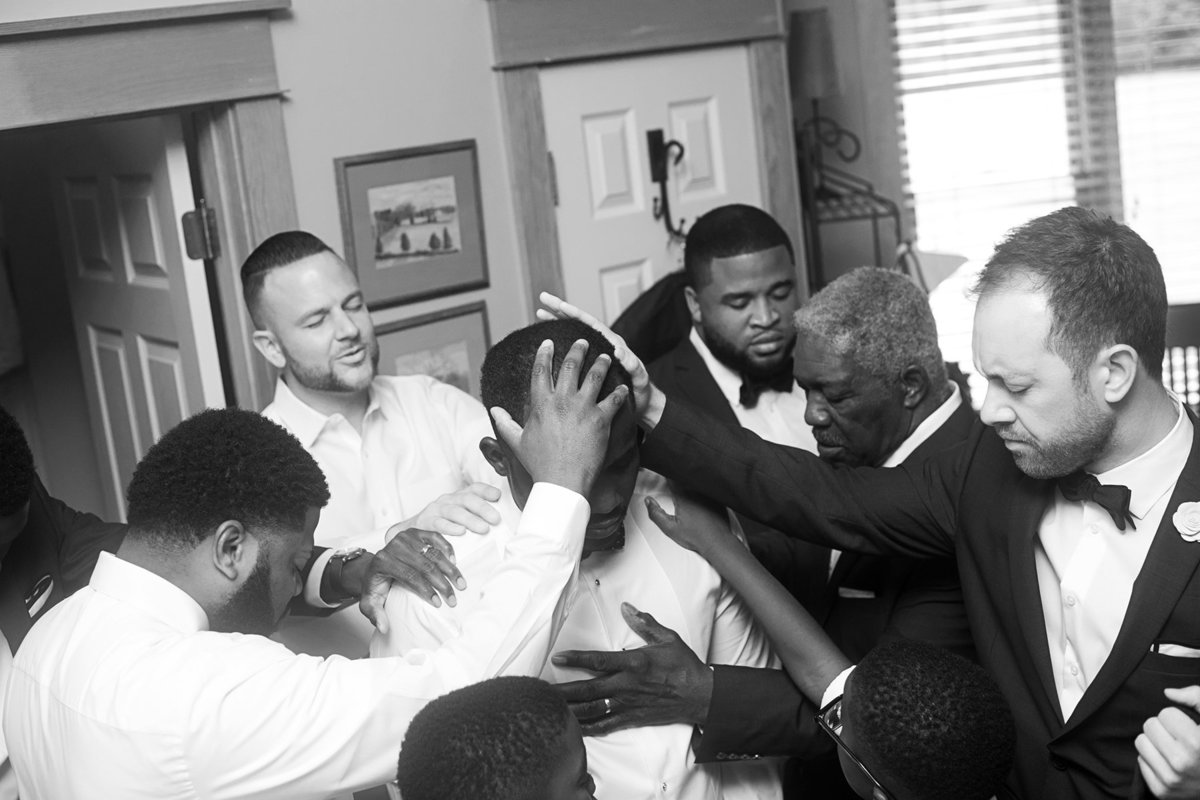 groomsmen praying over groom