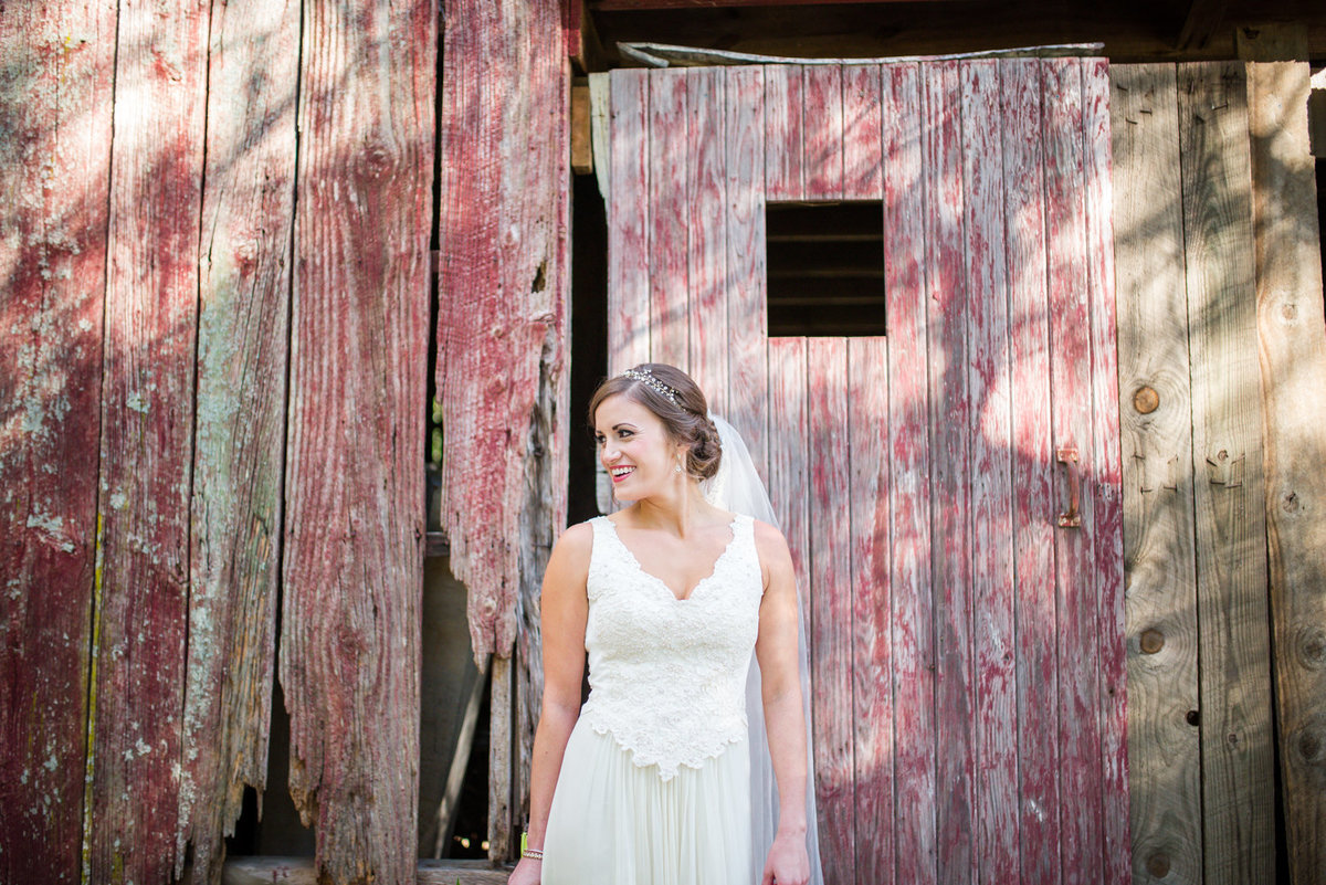 happy bride in front of red barn