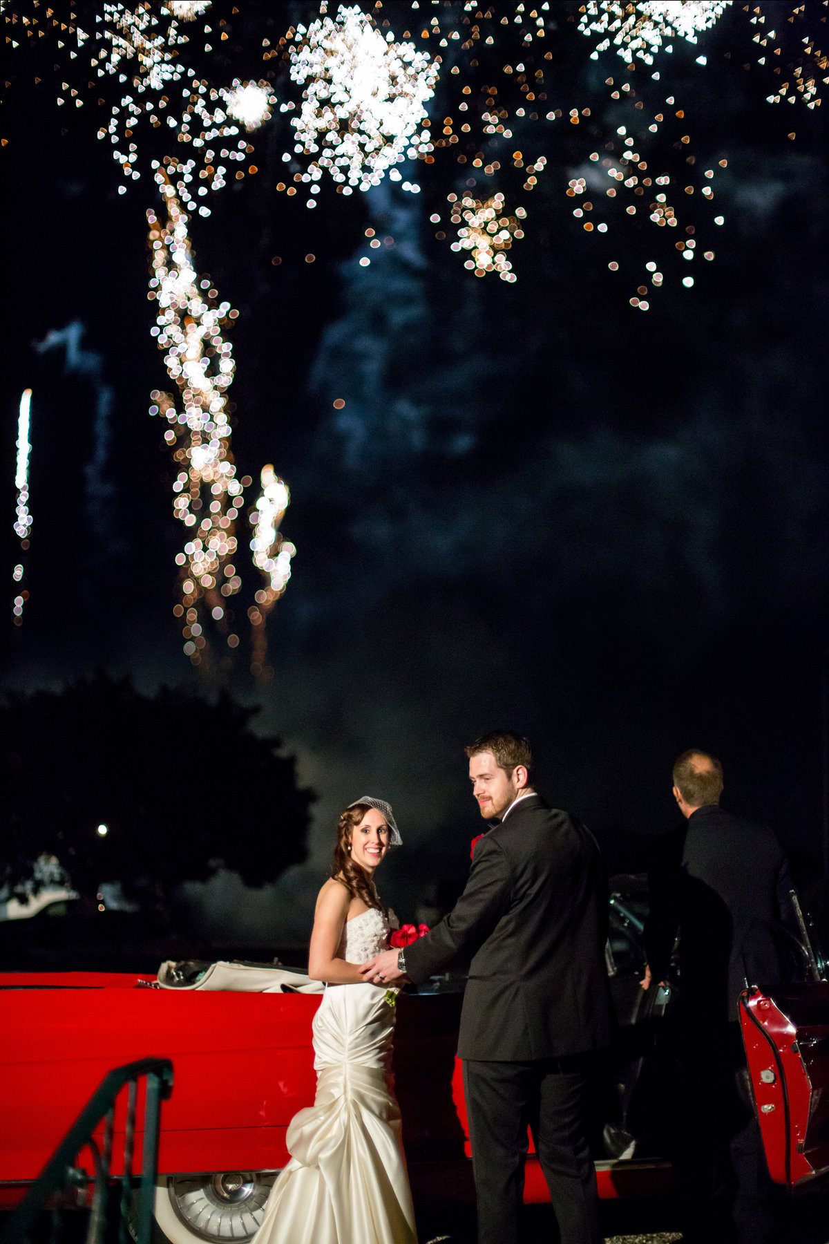 bride and groom exit wedding reception venue in classic car and fireworks at Oak Valley Vineyards Garden Ridge Texas