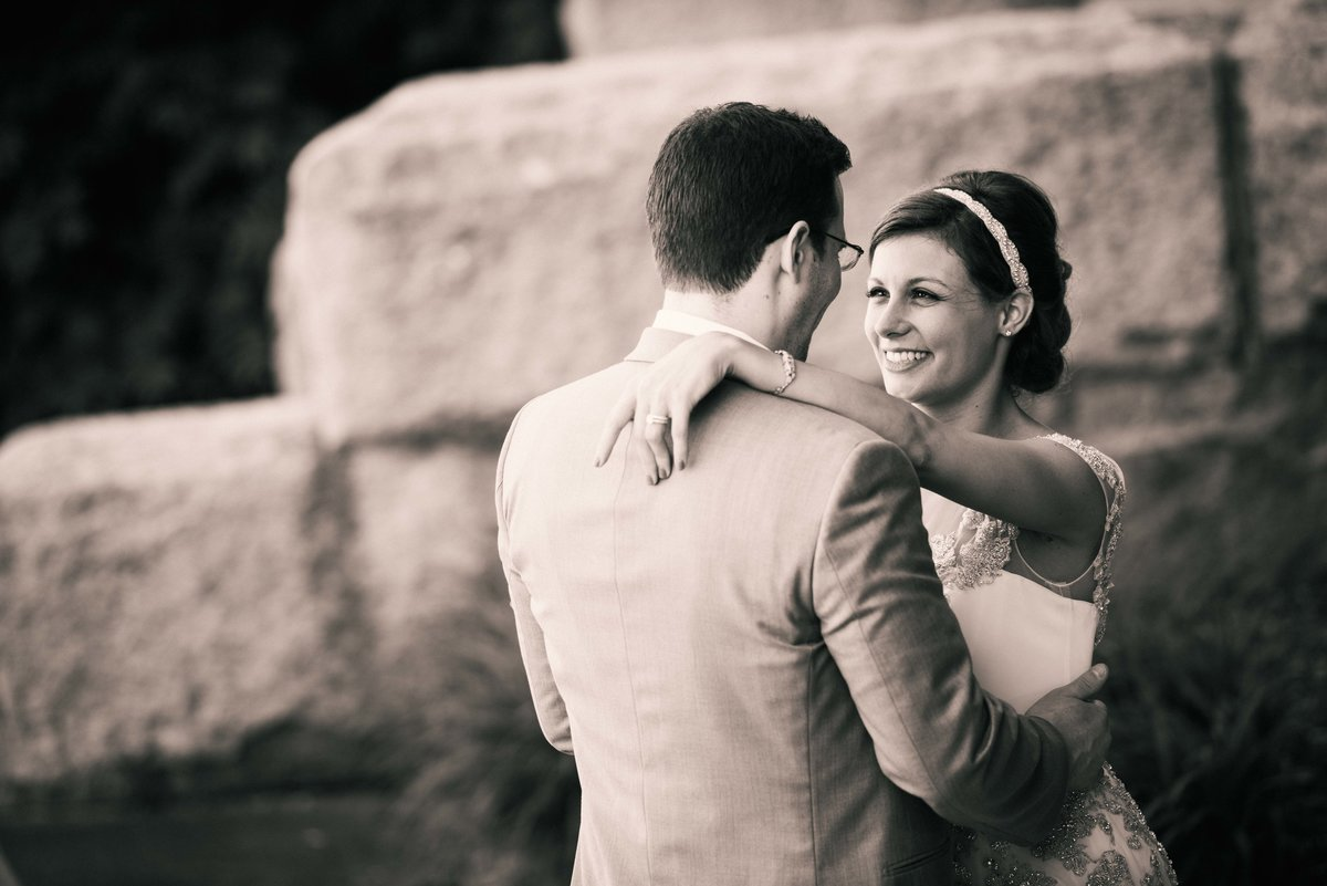 Bride and groom, ring showing, embrace, Lincoln Park Zoo, Chicago.