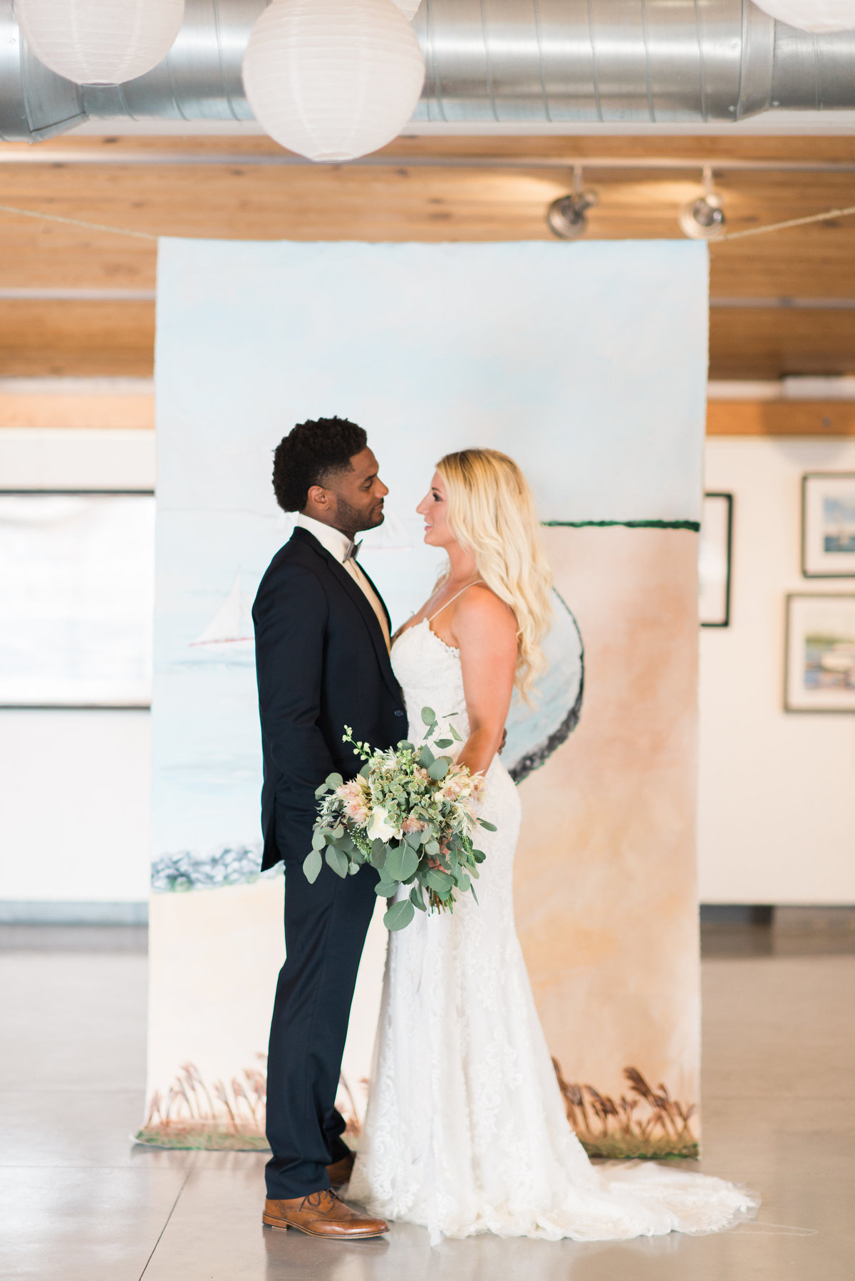 Bride and groom standing in front of Chesapeake Bay inspired  wedding backdrop By Brittany Branson as featured in What's Up Wedding Magazine