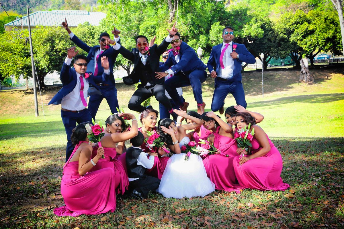 Fun, posed wedding party shot of groomsmen jumping over bridesmaids and bride. Photo by Ross Photography, Trinidad, W.I..