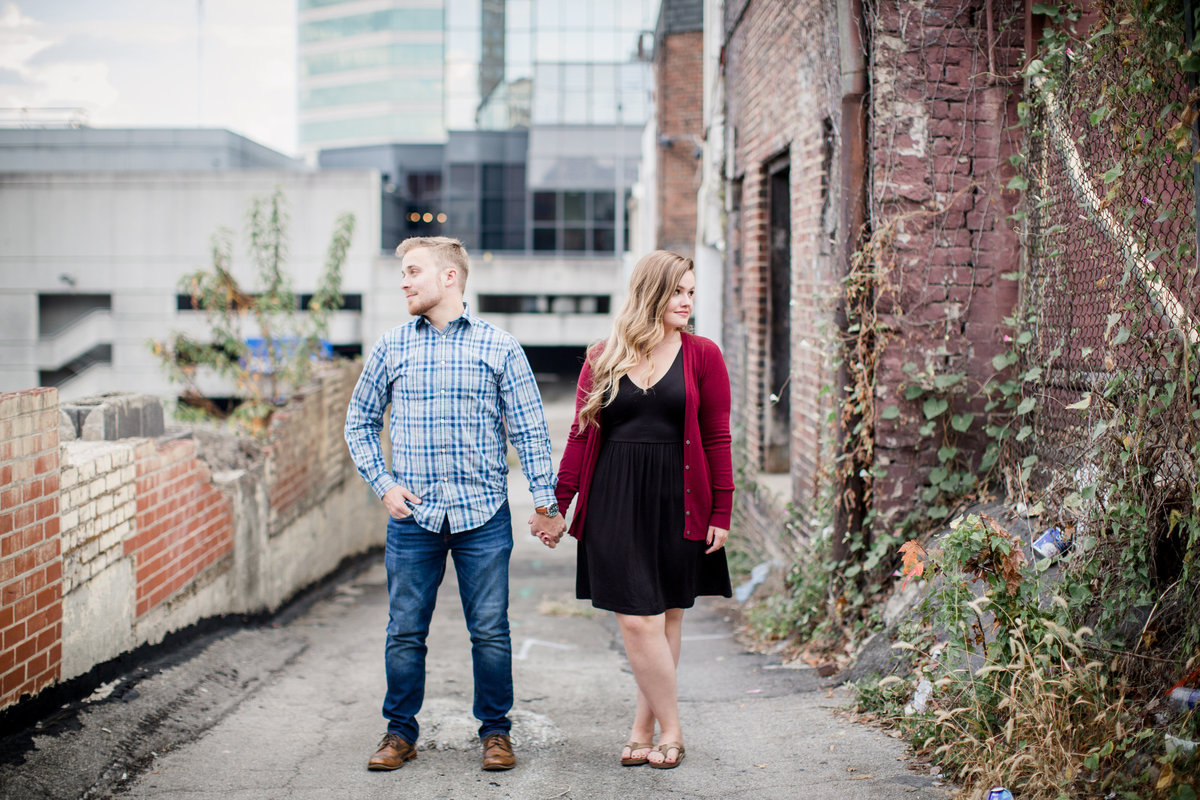 Standing hand in hand in an alley in Downtown Knoxville looking opposite directions engagement photo by Knoxville Wedding Photographer, Amanda May Photos.