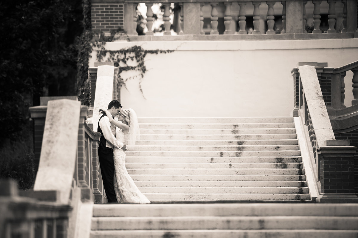 Bride and groom embrace on stairs at Mundelein Seminar, Chicago.