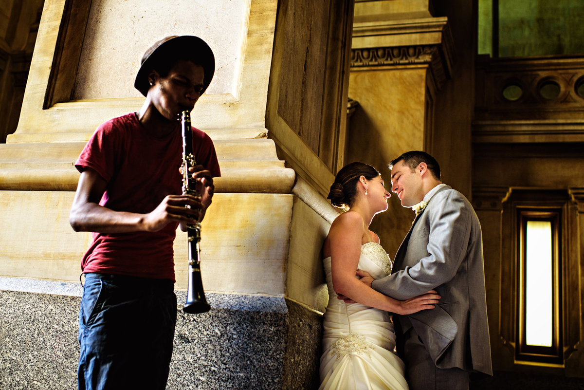 A man serenades a wedding couple at city hall in center city philadelphia.