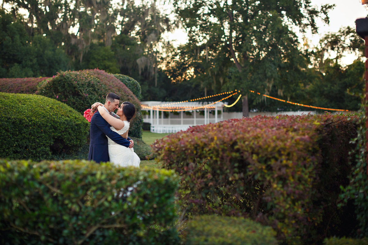 Bride and Groom Kissing in the garden with string lights