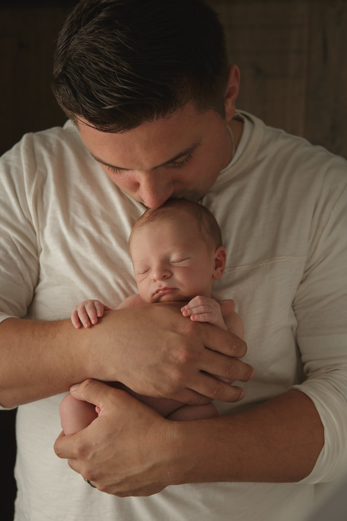 new dad kissing his newborn baby by Hudson Valley professional photographer in Cornwall NY photo studio