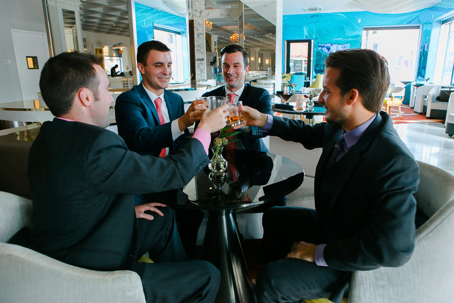 Groom before wedding with groomsmen having whisky shots and toasting