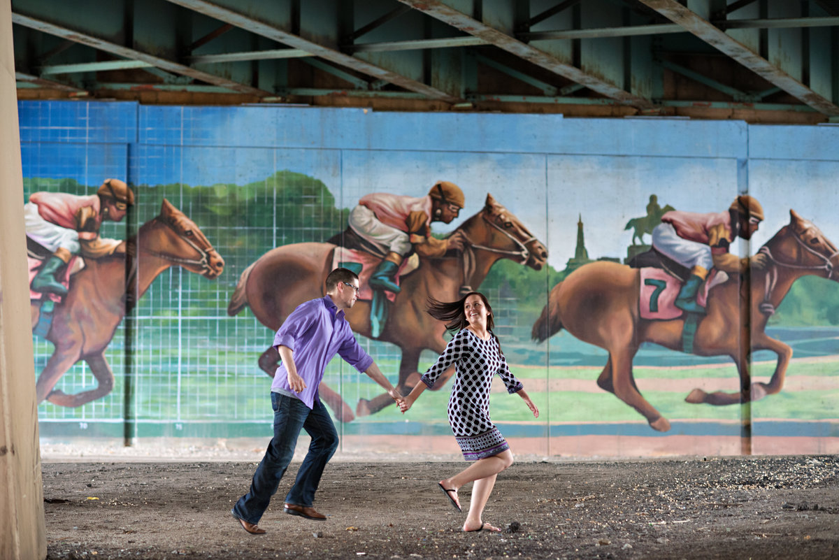 A bride to be runs with her fiance in front of a mural of a horse race in northern liberties.