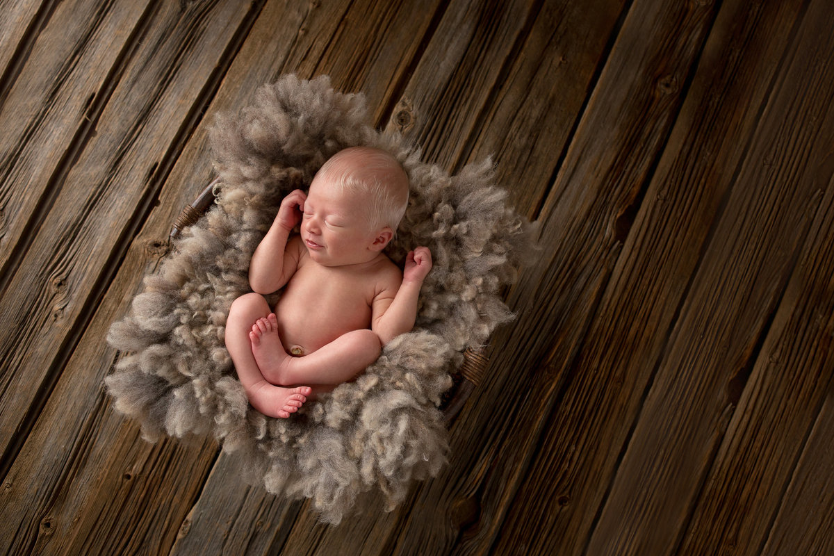Hudson Valley NY professional newborn photographer - blonde newborn baby boy photos in basket with wool on rustic barnwood floor in Cornwall NY