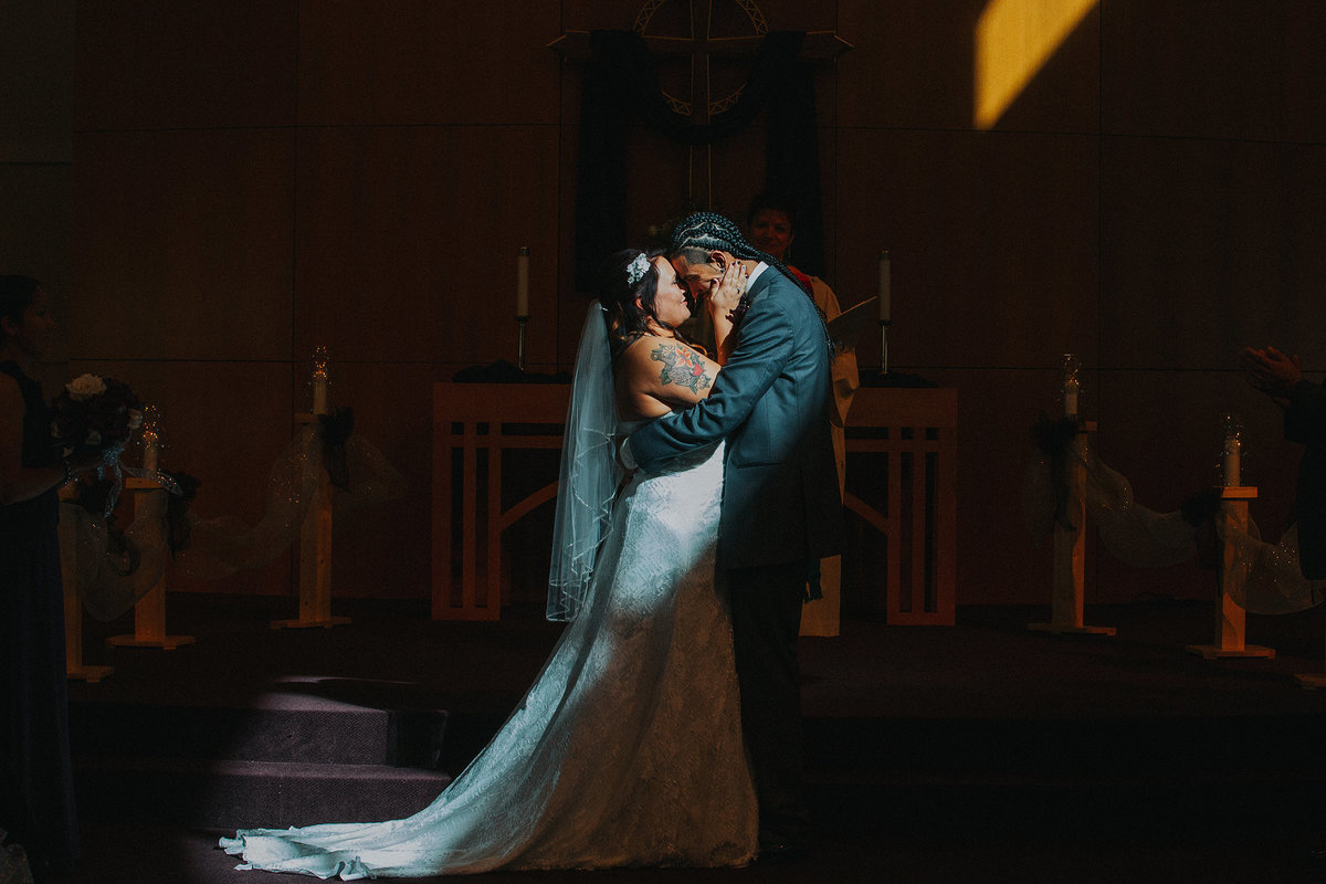 wedding couples first kiss at church altar