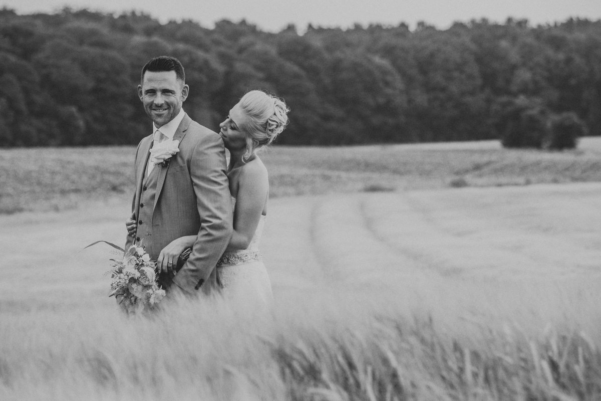 Bride & Groom stood in corn field.  Groom looking at camera as bride looks at groom - by Leeds Wedding Photographer Jono Symonds