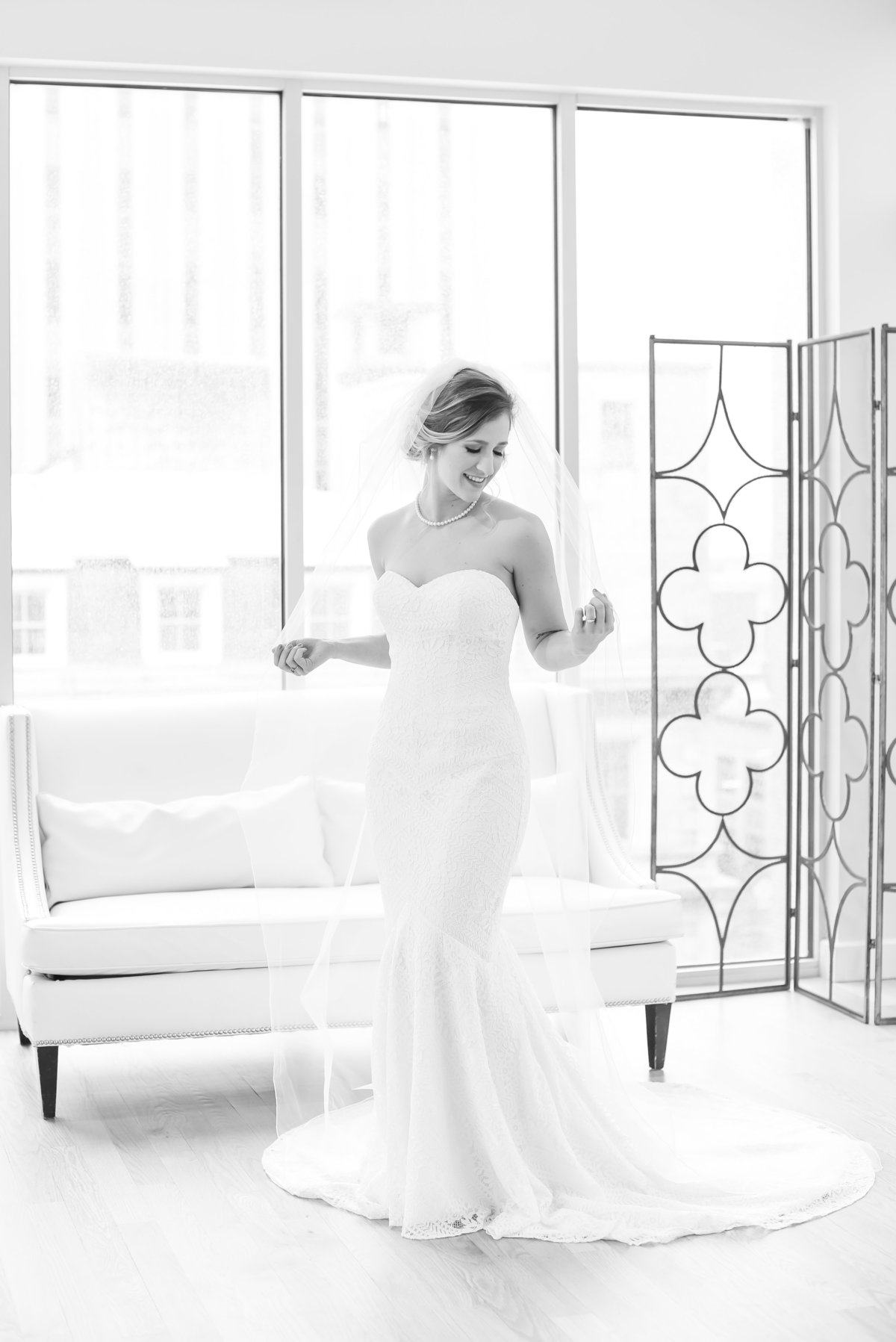 A bride wearing a strapless dress holding onto her cathedral length veil standing in front of a white leather couch at the Glass Box at 230 in Raleigh