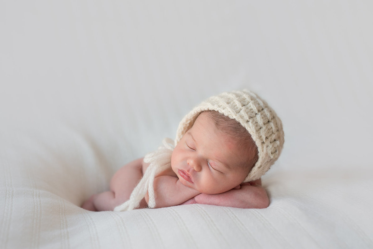 a newborn girl in a white bonnet