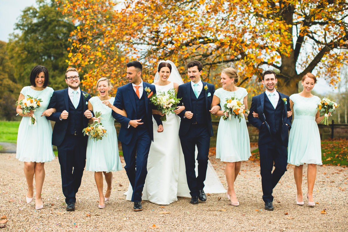 bridal party walking laughing at iscoyd park in autumn wedding