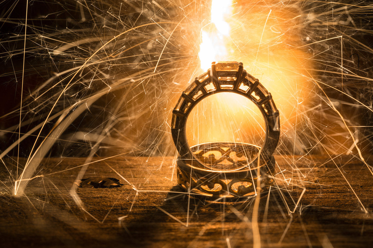 bride and groom wedding rings lite up by sparklers