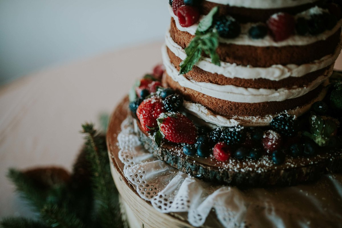 Beautiful berry naked wedding cake  sits on wood and lace at country club wedding in indianapolis