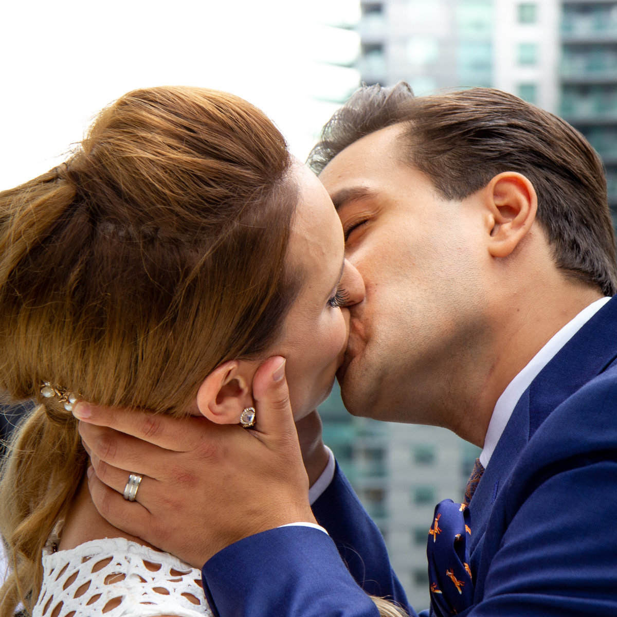 Bride and Groom share their first kiss at their Toronto rooftop wedding ceremony location