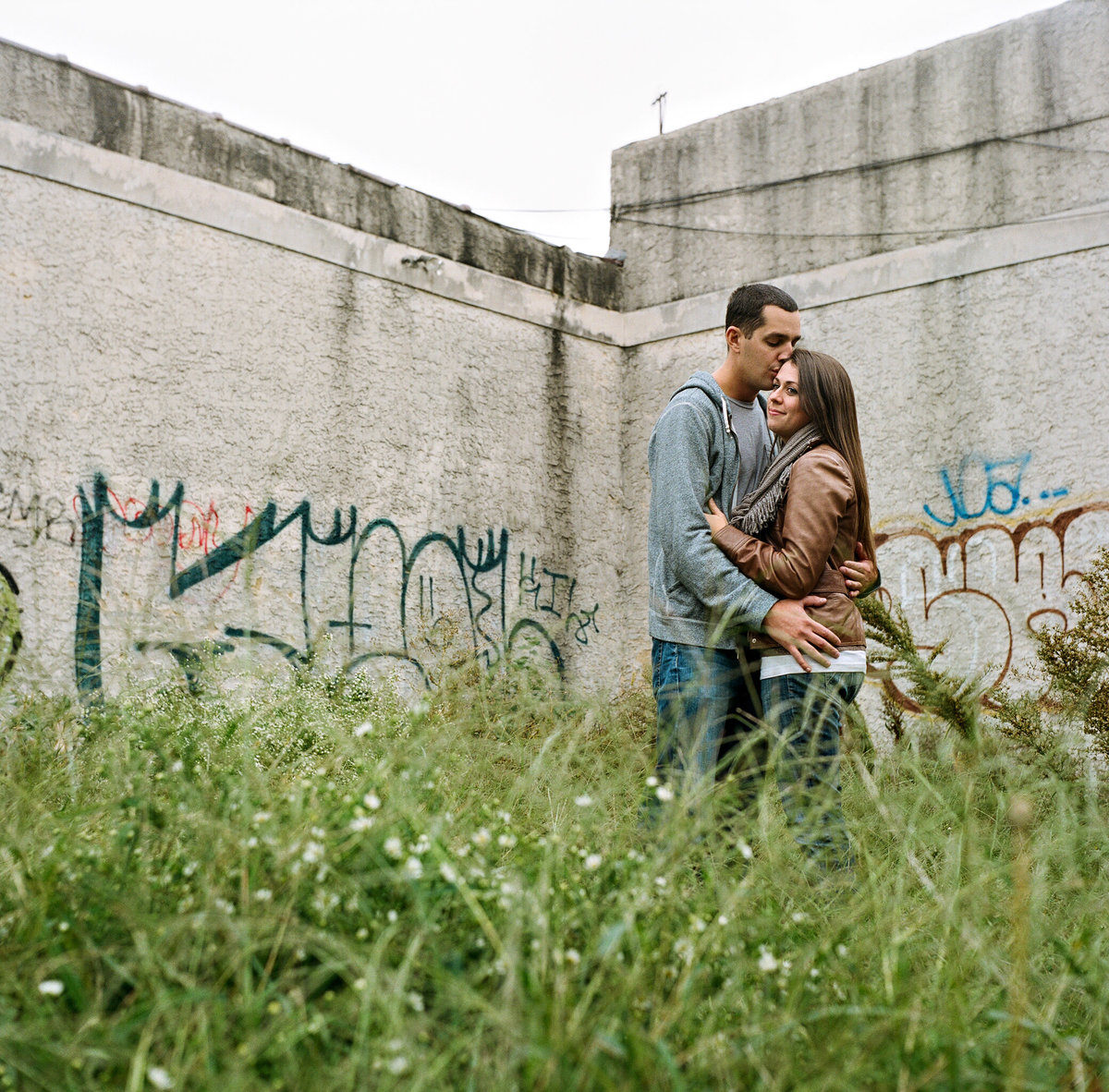 A couple stands in the tall grass in a vacant lot in philly.