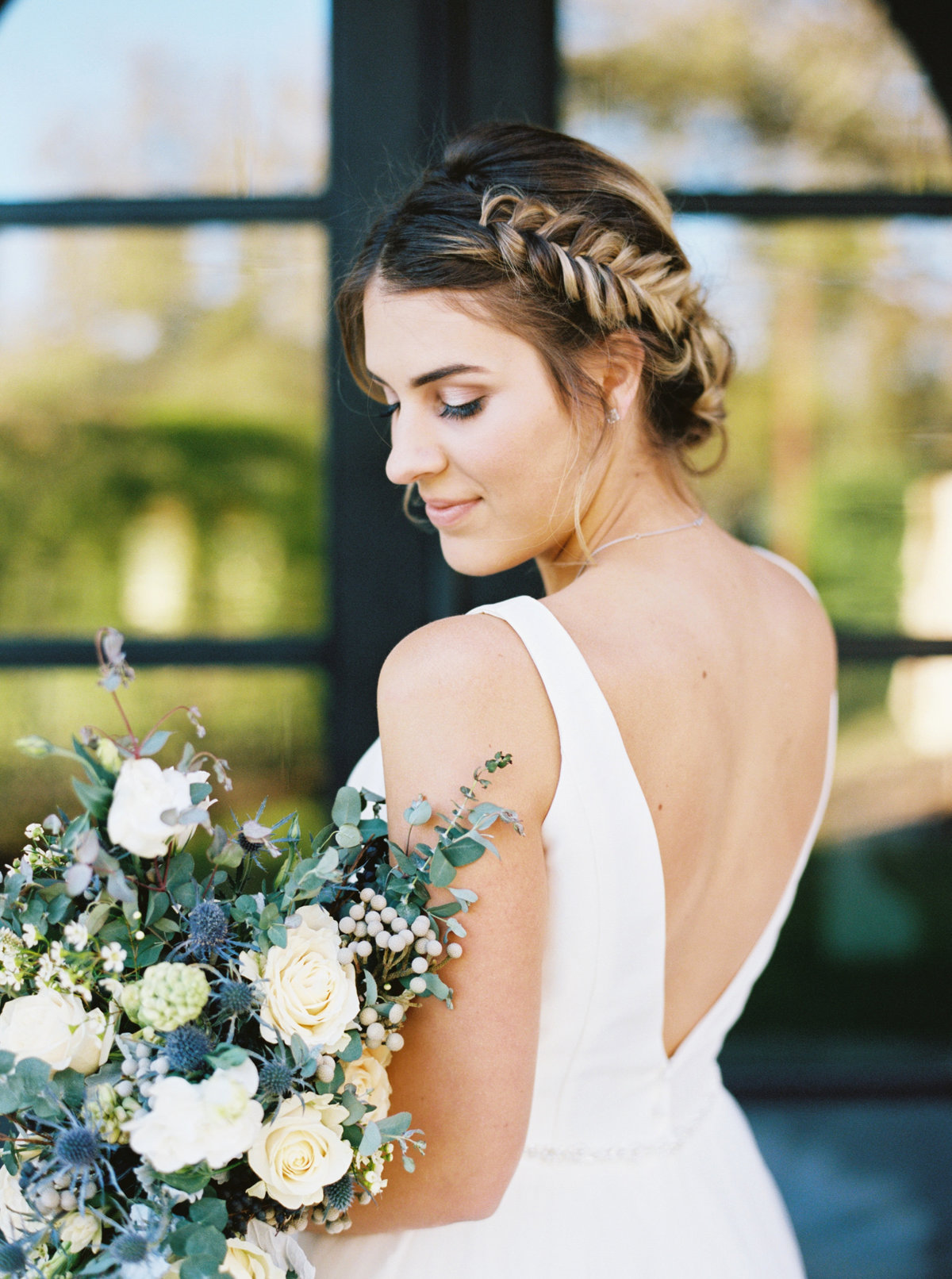 Bride with braided updo, A line wedding bridal dress, and her white and greenery bouquet.