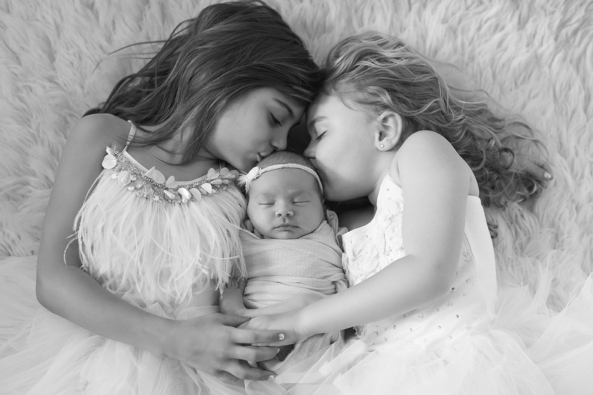 two older girls cuddle their new baby sister