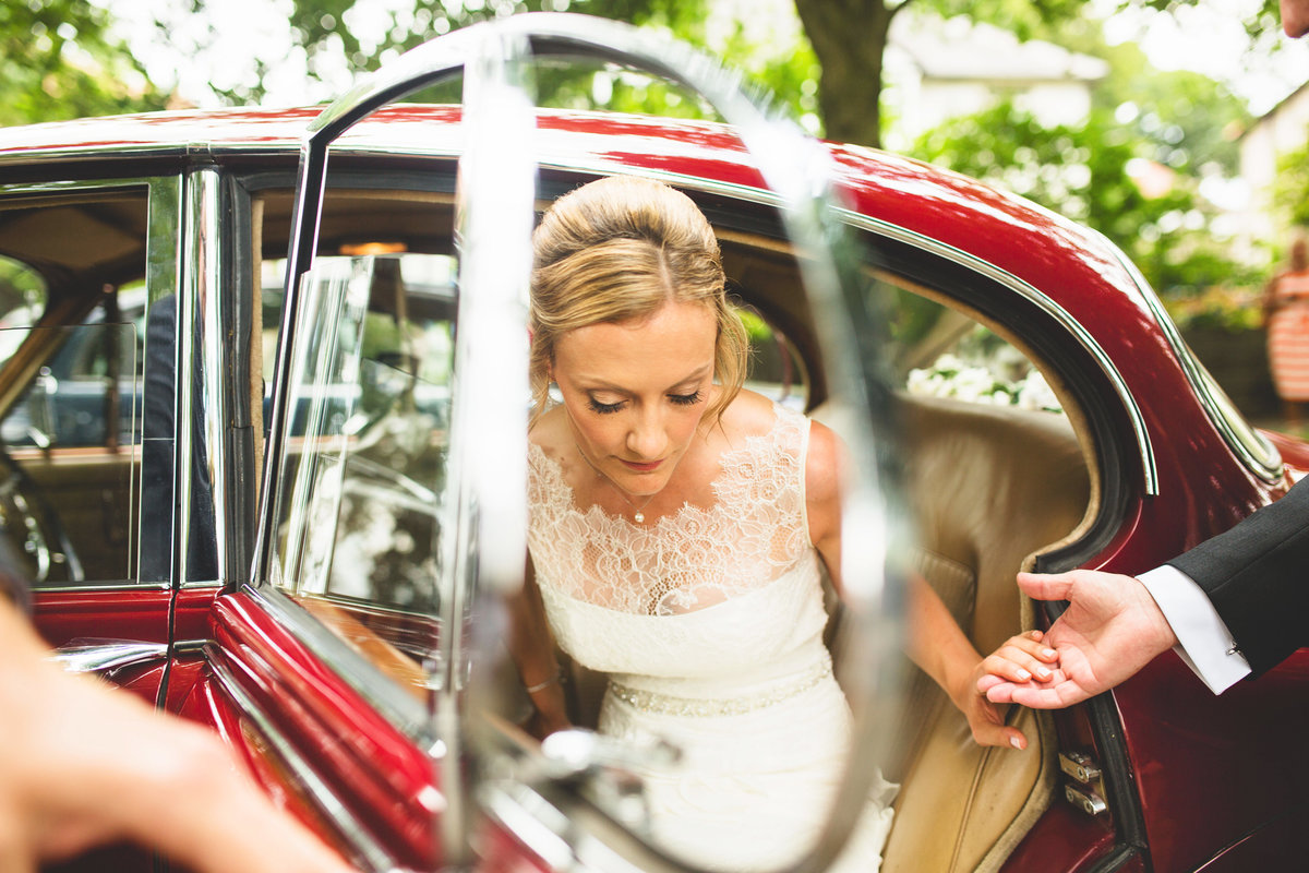 bride going to the wedding ceremony getting out of a red jaguar vintage car