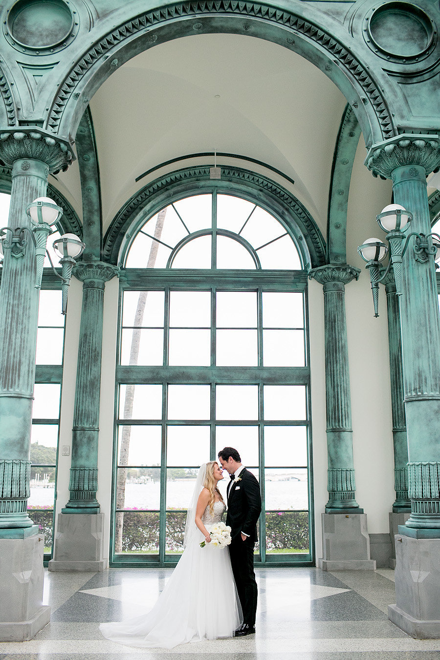 bride and groom standing in pavilion of flagler museum