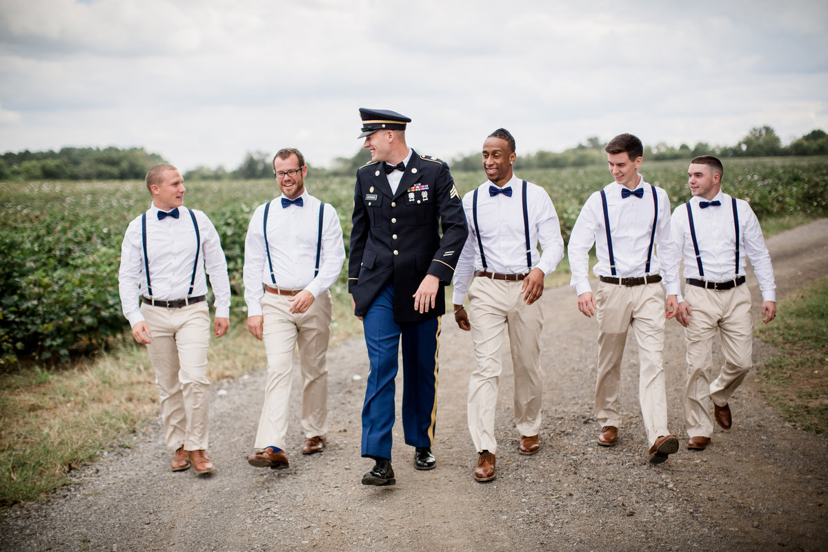 Groom walking with his groomsmen in front of cotton field at Sam Davis Home Wedding Venue by Knoxville Wedding Photographer, Amanda May Photos.