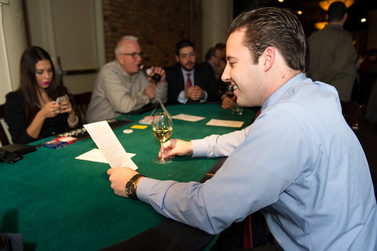 Man consults menu at Chicago poker fundraising event, Chicago IL.