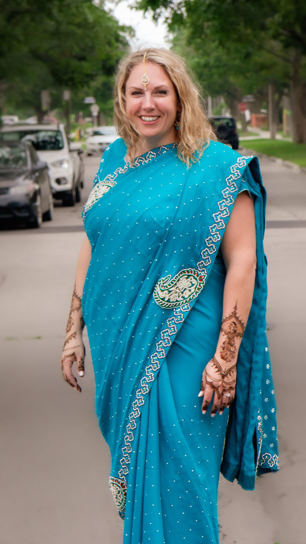 bride wearing a blue sari and her hands decorated with henna while she smiles and stands in the middle of the street with trees in the background