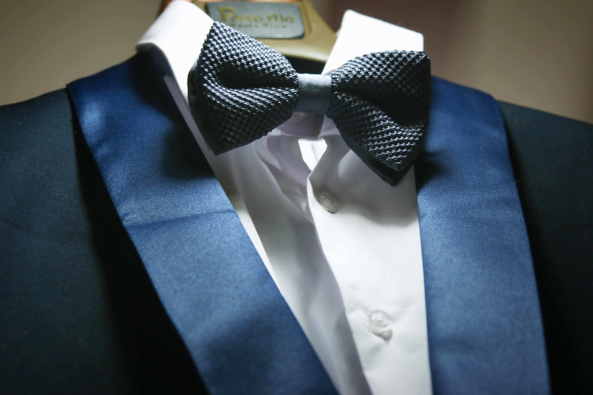 Close up of blue bow tie and tuxedo on a hanger. Photo by Ross Photography, Trinidad, W.I..