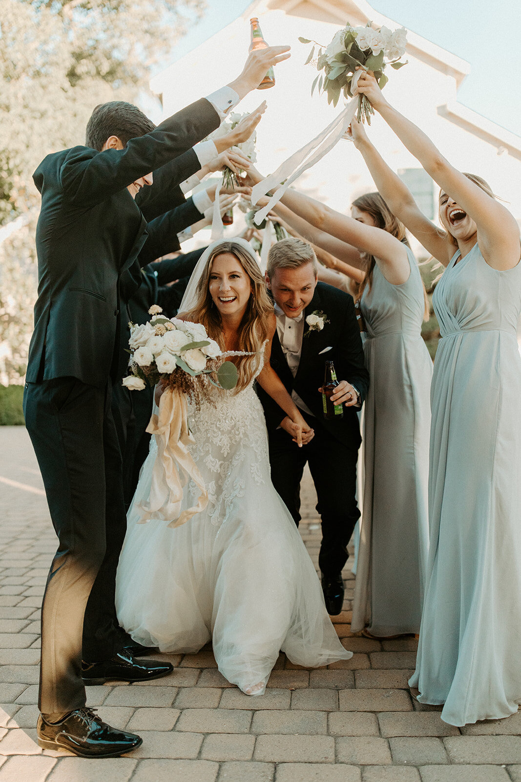 Bride and groom running under hands of bridal party