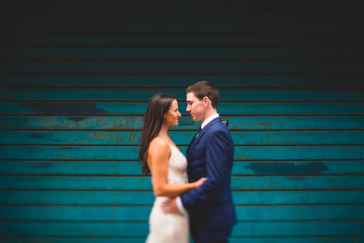 bride and groom looking at each other in front of a teal blue garage door