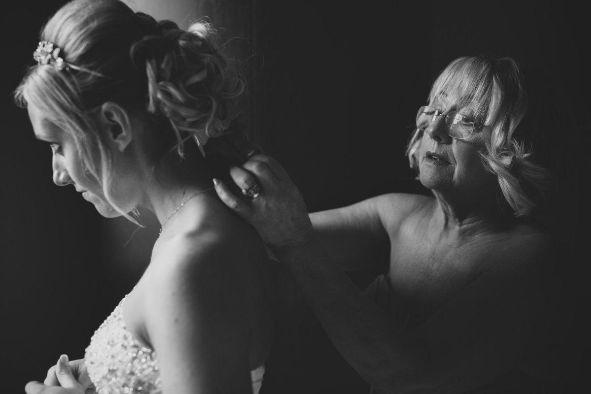 bride by the window with her mum fastening her necklace
