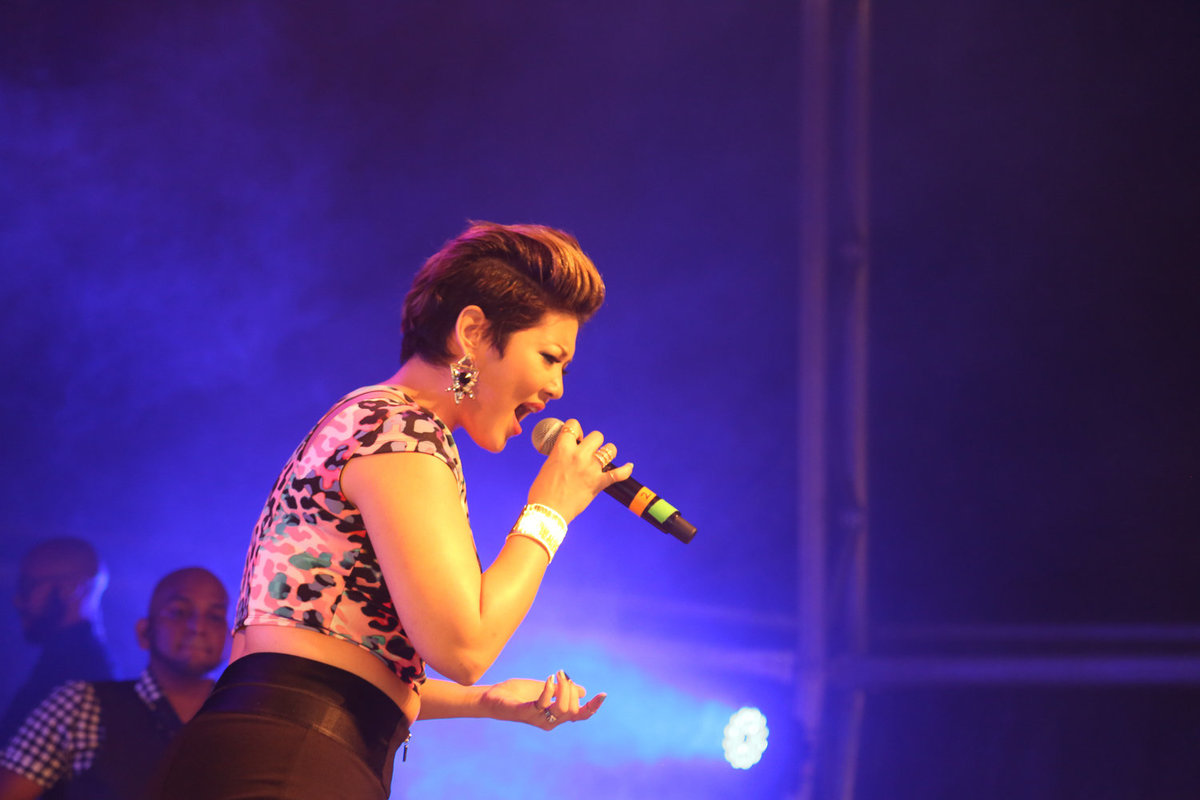 International star, Jamaican singer Tessanne Chin sings under purple lights. Photo by Ross Photography, Trinidad, W.I..