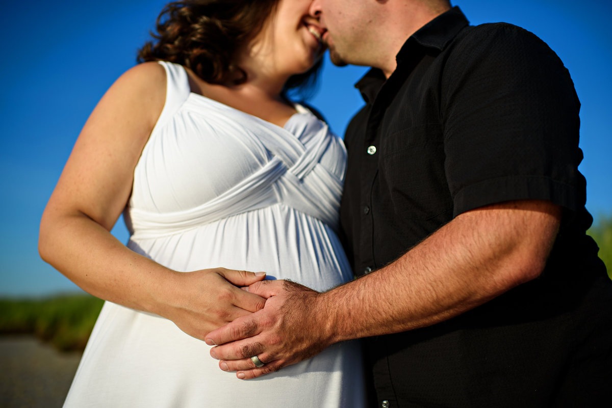 A husband and wife place their hands on her pregnant belly on the beach.