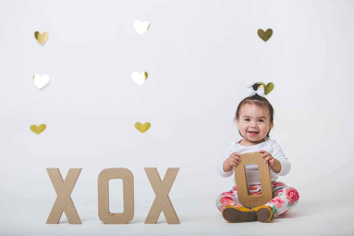 Baby with XOXO letter props in front of a heart backdrop in photography studio