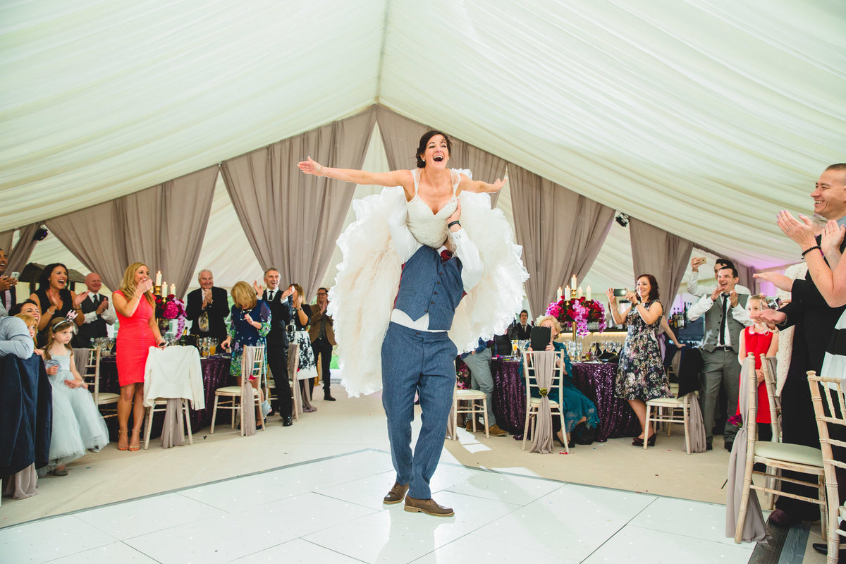 a dramatic choreographed first dance. groom is lifting the bride