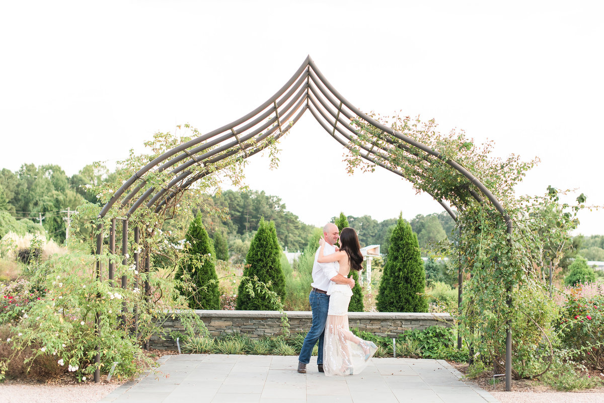 bride and groom kissing underneath a grand arbor in the middle of a garden at JC Raulston Arboretum