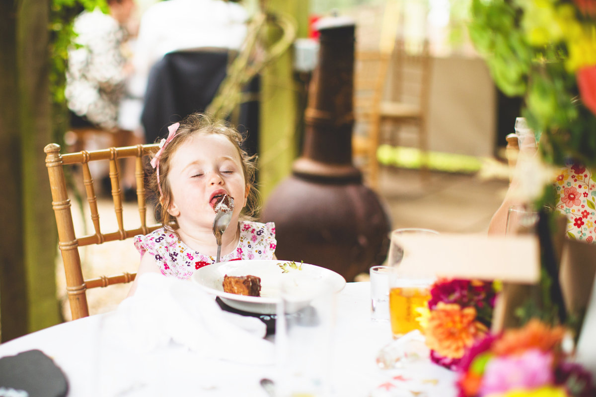 funny wedding photo of girl licking cake off the spoon with her eyes closed