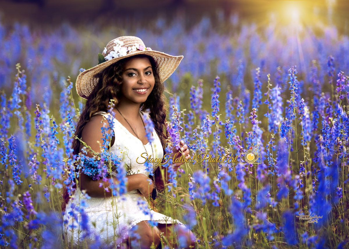 senior girl sitting in field of flowers