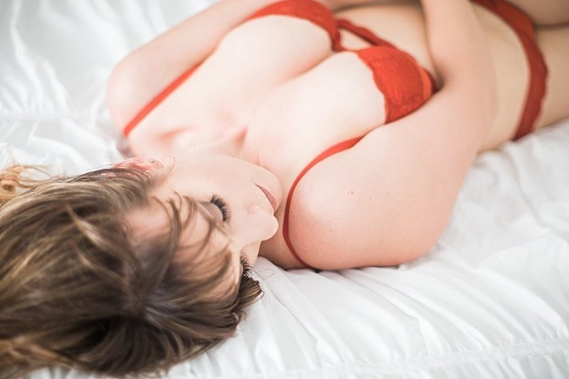 woman laying on bed sensually in bedroom in burnt orange victorias secret bra and panty set