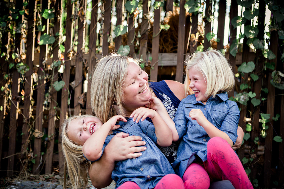 Mom and her two twin girls sitting in a garden for their family pictures by Knoxville Wedding Photographer, Amanda May Photos.