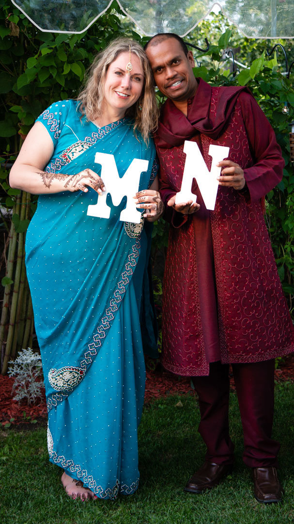 married couple holding their initials in their Toronto backyard wedding ceremony site with bride wearing a blue sari