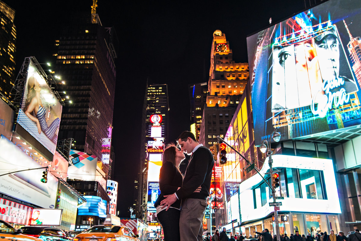 A newly engaged couple hold each other in Time Square.